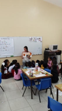 """Stephanie teaching colors in English. """"Rainbow Song"""" is posted on the white board behind her."""