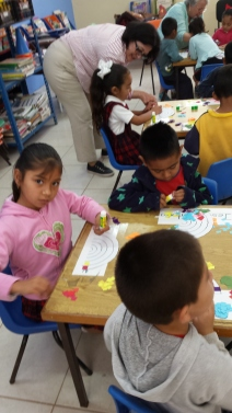 Children making their own rainbows with colored bits of paper and glue.