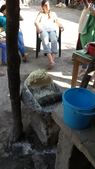 the stone mortar and pestle for grinding, with some of the dough