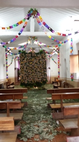 Floor of the church covered with leaves and pine needles. Altar hidden by a barrier of palm leaves and fruit with coconuts at the base. Lit candles under and behind the barrier.