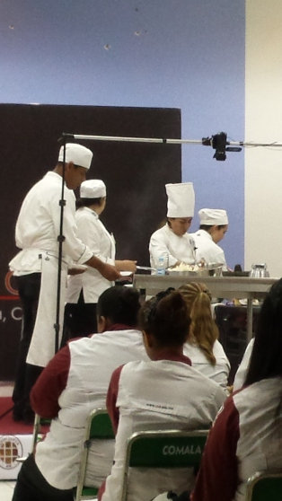 Cooking on the stage. Culinary students in the audience with their maroon and white uniforms.