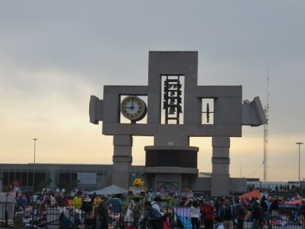 Large clock and sculpture on the border of the plaza where the pilgrims camp out.